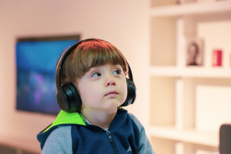 hearing loss in seniors starts early --- young boy with headphones